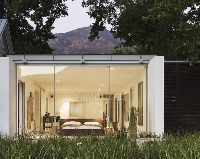 Стеклянная стена современного дома против гор — стоковое фото