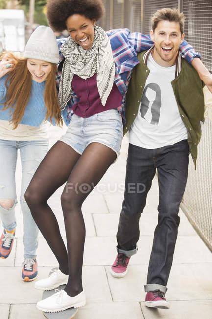 Счастливые молодые друзья, смеющиеся на городской улице — стоковое фото
