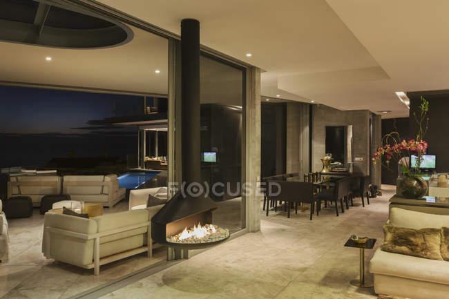 Illuminated luxury modern home showcase interior with hanging fireplace — Stock Photo