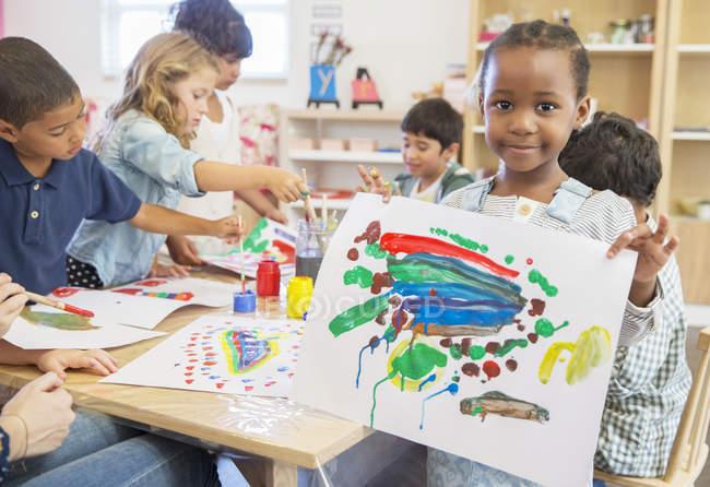 Étudiant montrant la peinture au doigt en classe — Photo de stock