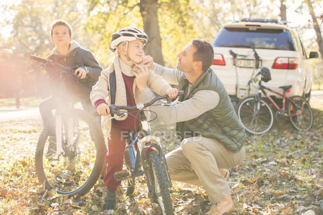 Padre casco di fissaggio del figlio in bicicletta nei boschi autunnali — Foto stock