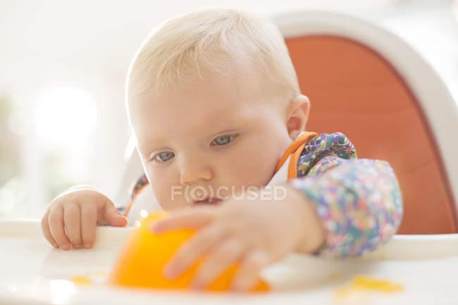 Дівчинка, граючи з желатину десерт у дитячий стілець — стокове фото
