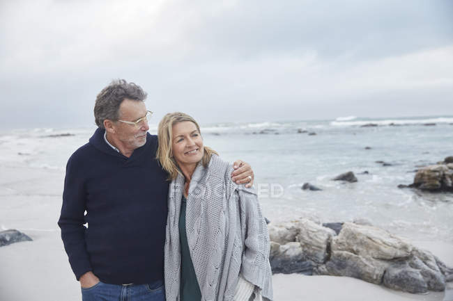 Affectionate couple hugging on winter beach together — Stock Photo
