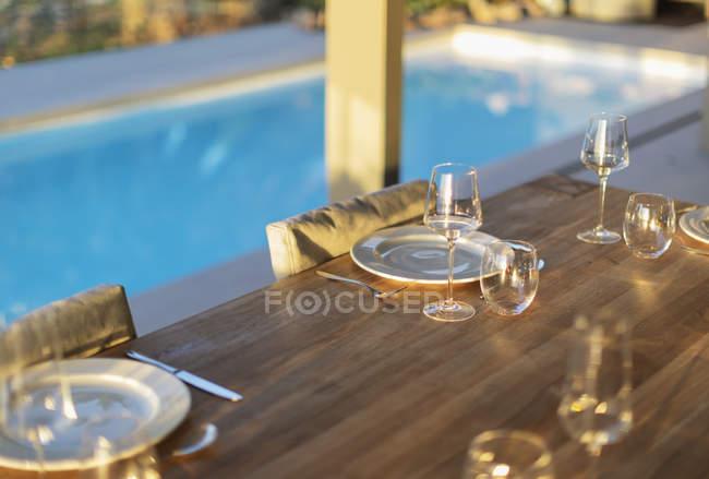 Placesettings en mesa de madera patio al lado de la piscina - foto de stock