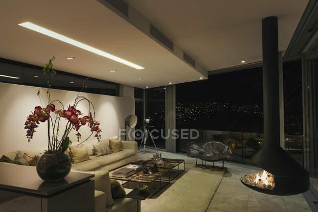 Lareira de luxo moderno e casa vitrine sala de estar à noite — Fotografia de Stock