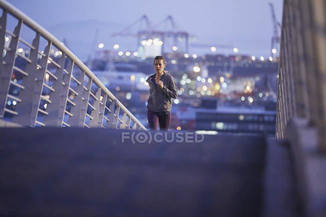 Female runner running on urban footbridge at dawn — Stock Photo