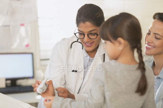 Kinderärztin zeigt Patientin und Mutter digitales Thermometer im Untersuchungsraum — Stockfoto