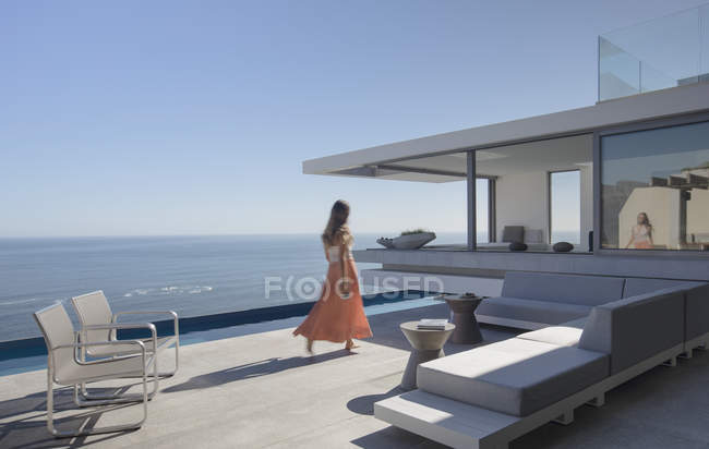 Woman in dress walking on sunny, modern, luxury home showcase exterior patio with ocean view — Stock Photo