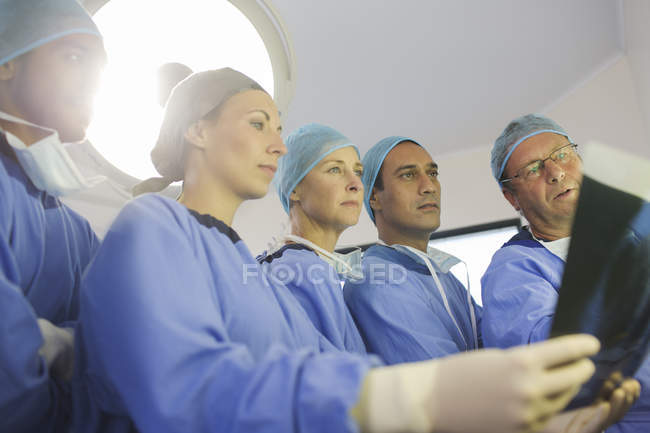 Surgeons looking at x-ray during surgery in operating theater — Stockfoto