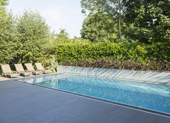 Sedie a sdraio a bordo piscina — Foto stock