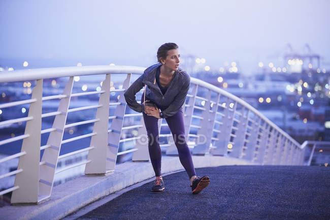 Жіночий бігун розтягування ногу на міських місток — стокове фото
