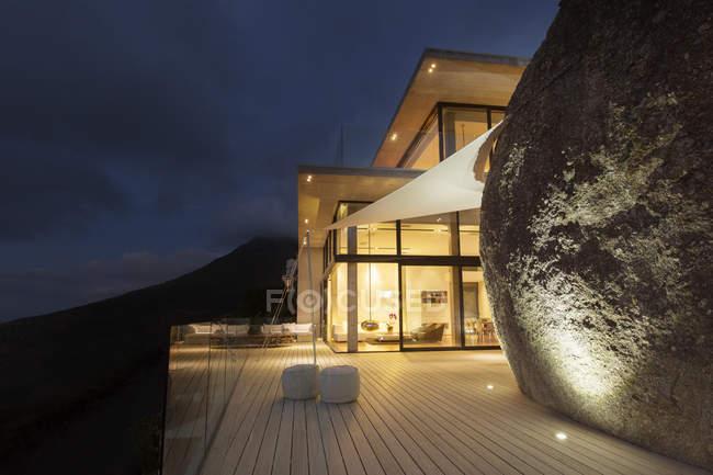 Иллюминированный современный дом с видом на скалу и балконом — стоковое фото