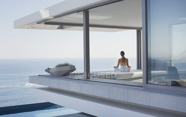 Femme sereine méditant sur moderne, maison de luxe vitrine patio extérieur avec vue sur l'océan — Photo de stock