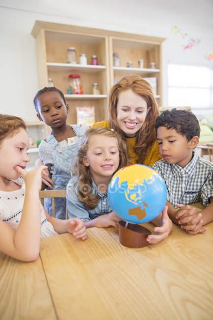 Студенты и преподаватели проверяют глобус в классе — стоковое фото