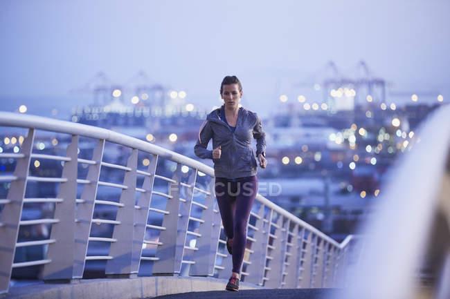 Женщина бегущая по городскому пешеходному мосту на рассвете — стоковое фото
