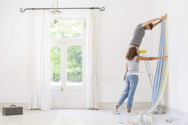 Couple hanging wallpaper together — Stock Photo