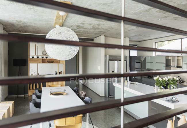 Blick auf moderne Esszimmer und Küche durch Holzleisten — Stockfoto