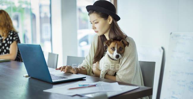 Жінка тримає собаку і роботи в офісі — стокове фото