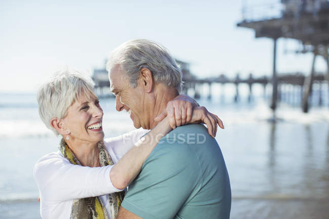 Senior couple hugging on beach — Stock Photo