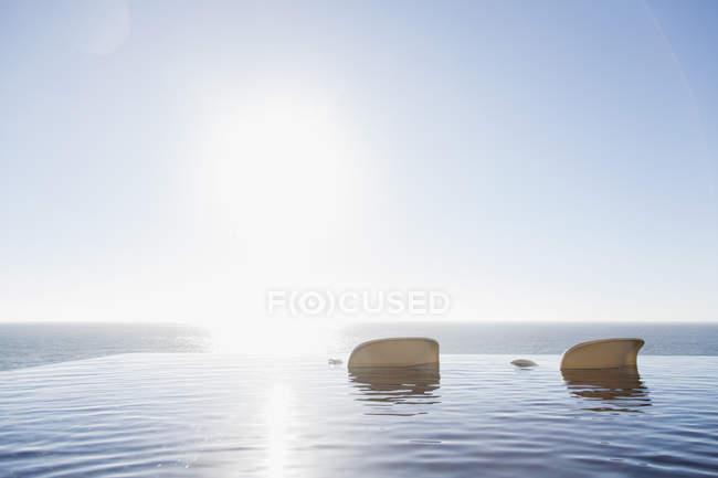 Садовые стулья в бассейне с видом на океан — стоковое фото