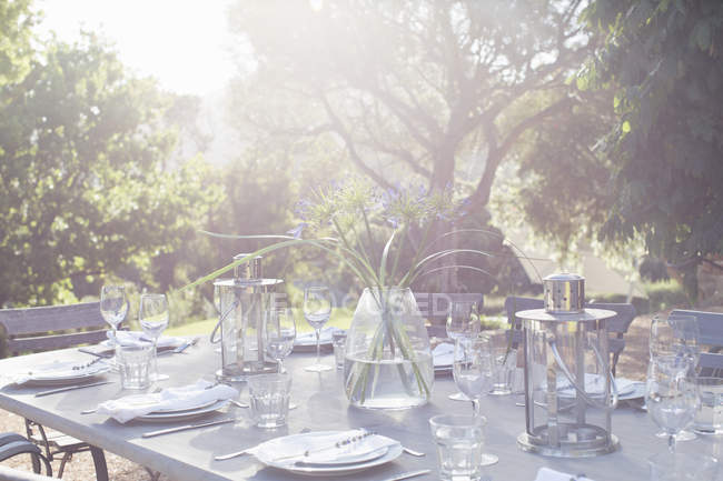 Place settings on sunny patio table — Stock Photo