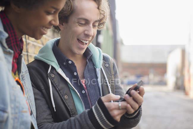Couple utilisant un téléphone portable sur la rue de la ville — Photo de stock