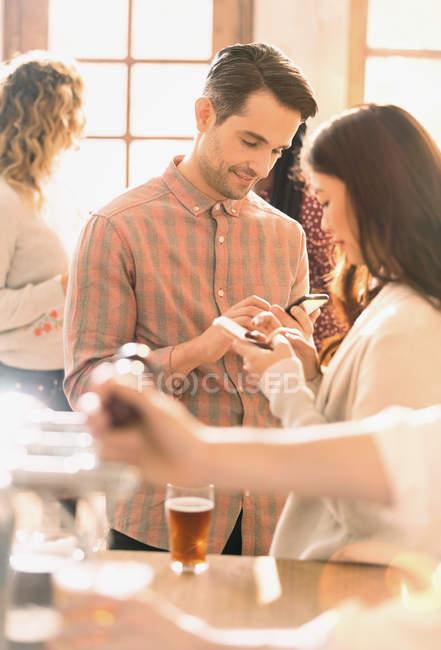 Mensagens de casal com telefones celulares no bar — Fotografia de Stock