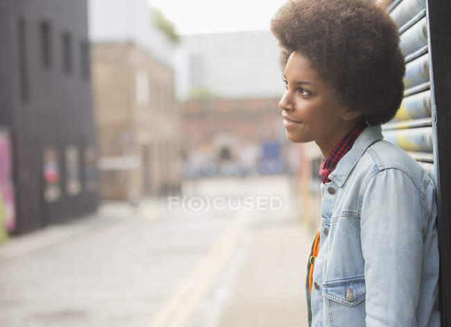 Pensive woman standing on city street — Stock Photo