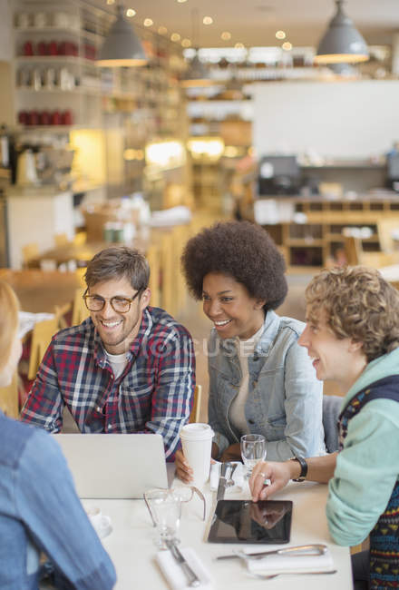 Happy young friends talking in cafe — Stock Photo