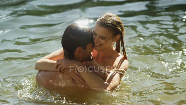 Affectionate couple hugging and swimming in sunny lake — Stock Photo