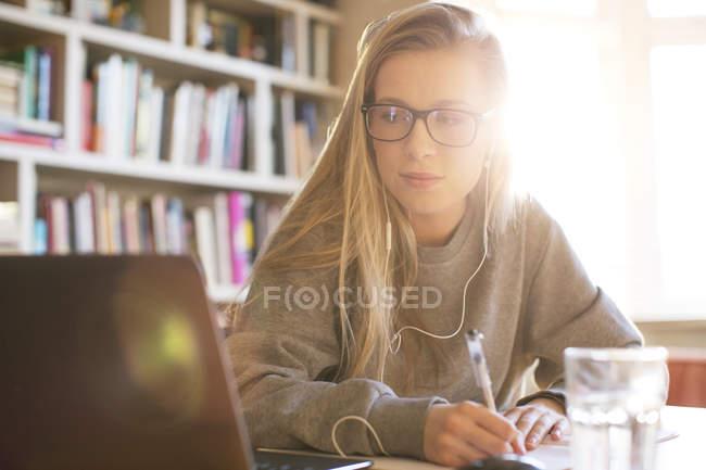 Adolescente com fones de ouvido fazendo lição de casa com laptop — Fotografia de Stock
