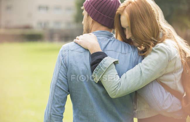 Feliz jovem casal abraçando no parque — Fotografia de Stock