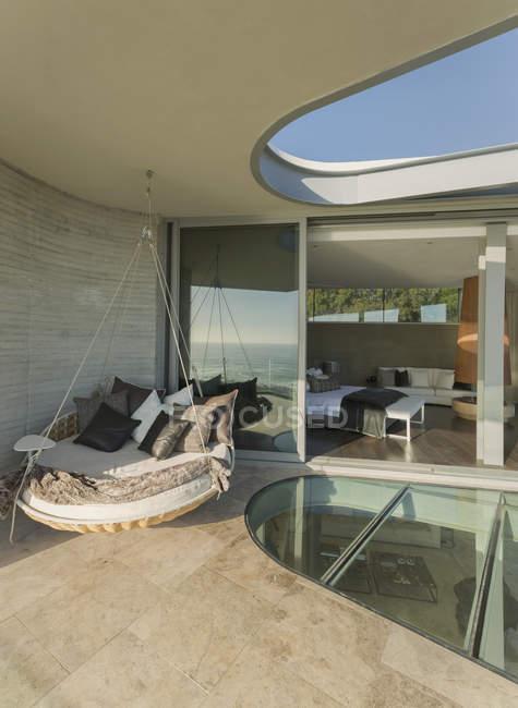 Hanging cushion bed on modern luxury home showcase patio — Stock Photo