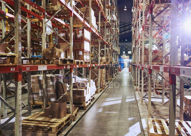 Marchandises empilées sur des étagères dans un entrepôt de distribution — Photo de stock