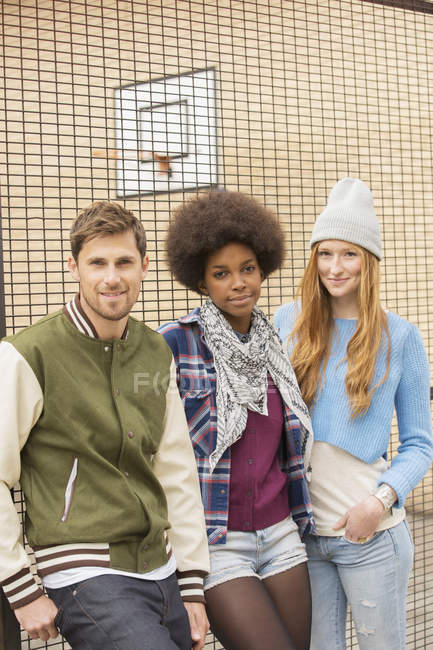 Friends smiling outside urban basketball court — Stock Photo