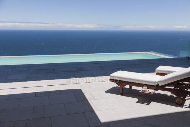 Lounge chairs and infinity pool overlooking ocean — Stock Photo