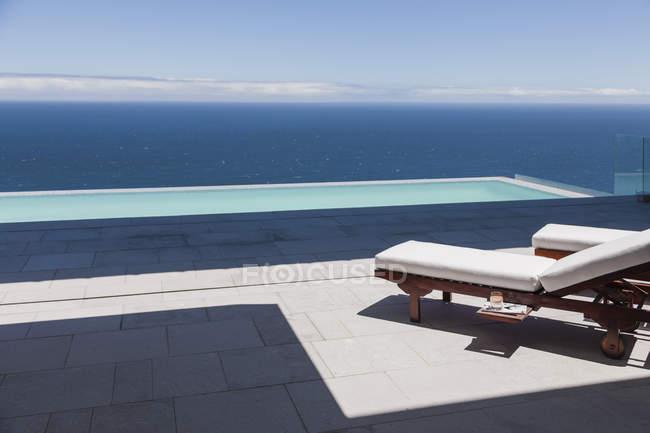 Гостиные стулья и бассейн с видом на океан — стоковое фото