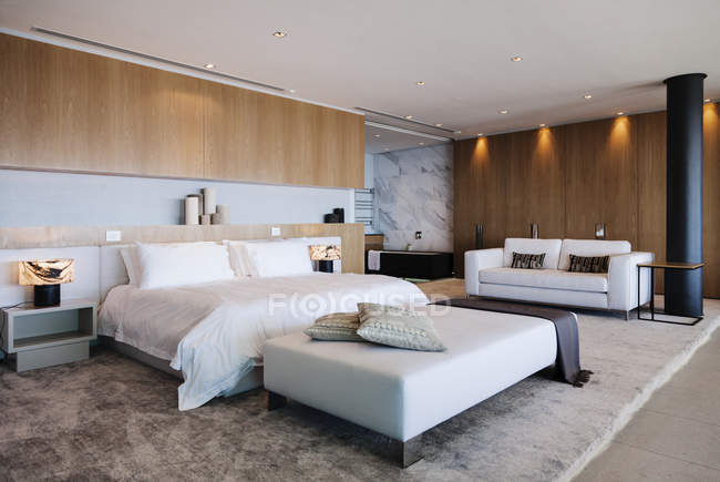 Bed and sofa in modern bedroom — Stock Photo