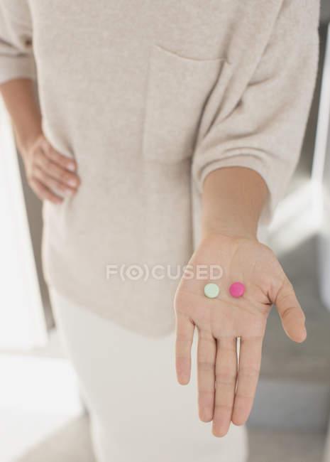 Mujer llevando a cabo, mostrando dos pastillas, rosas y verdes - foto de stock