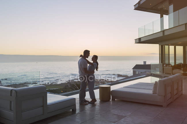 Affectionate couple hugging on luxury patio with ocean view — Stock Photo