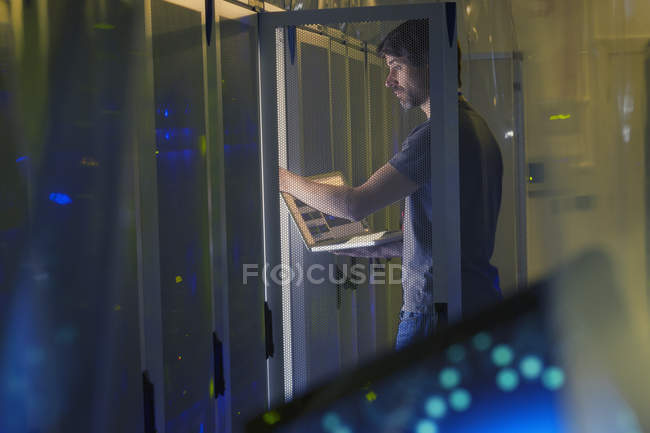 Server room technician with laptop at panel — Stock Photo