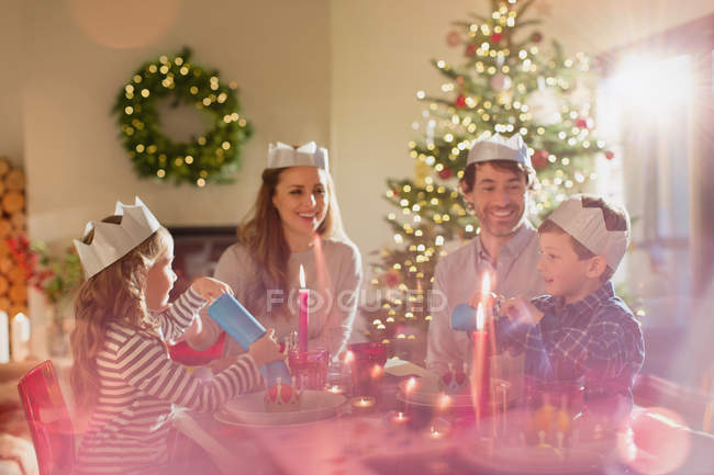 Family wearing paper crowns at Christmas dinner table — Stock Photo
