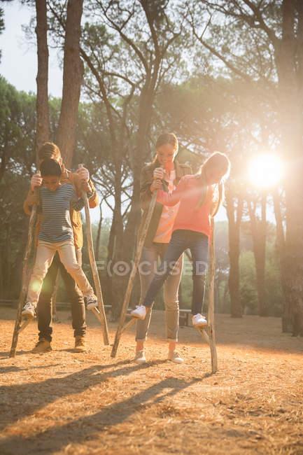 Teachers helping students walk on stilts — Stock Photo