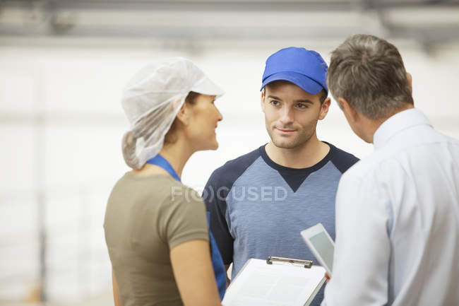 Supervisor and workers talking in food processing plant — Stock Photo