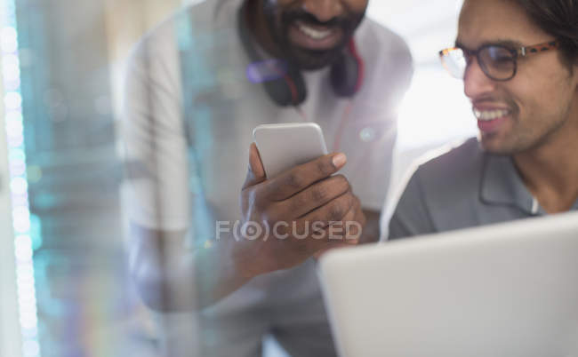 Smiling creative businessmen using smart phone — Stock Photo