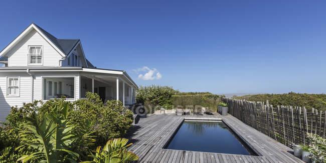 Casa branca vitrine exterior e piscina sob céu azul ensolarado — Fotografia de Stock