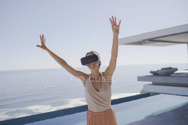 Energische Frau mit Virtual-Reality-Simulator-Brille auf moderner, luxuriöser Wohnvitrine Außenterrasse mit Meerblick — Stockfoto