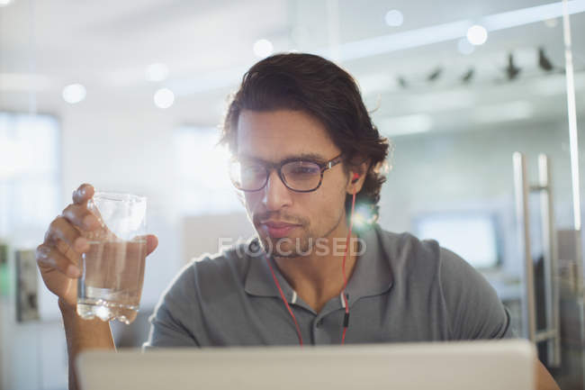 Focused businessman with headphones drinking water at laptop — Stock Photo