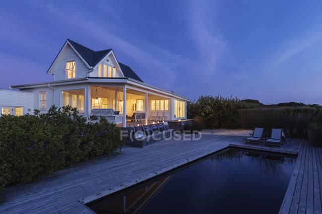 Iluminado casa branca vitrine exterior e piscina à noite — Fotografia de Stock