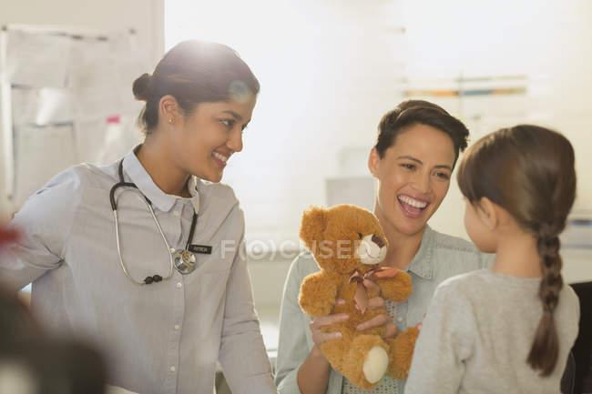 Lächelnde Kinderärztin und Mutter zeigt Teddybär Patientin im Untersuchungsraum — Stockfoto